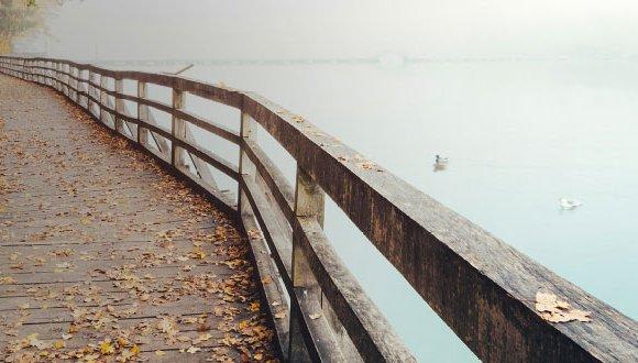Boardwalk near sky blue water