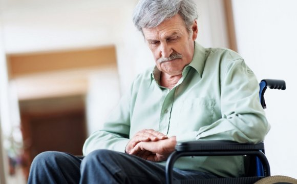 An elderly man sits in a